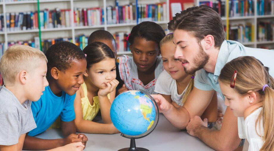 Jeunes enfants eleves et leur professeur etudiant la geographie avec un globe terrestre en salle de classe